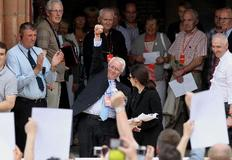 Συγγενείς των θυμάτων κρατούν φωτογραφίες τους και ξεσπούν σε χειροκροτήματα τη στιγμή που απολογείται ο Βρετανός πρωθυπουργός