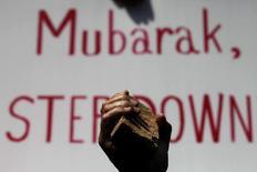 «Μουμπάρακ παραιτήσου» γράφει το πλακάτ, πίσω από τον διαδηλωτή που κρατά την πέτρα...
