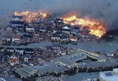 Στις φλόγες σπίτια που παρέσυρε το τσουνάμι στην πόλη Νατόρι.