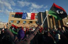 Η γαλλική σημαία στην πρόσοψη ενός δικαστηρίου στη Βεγγάζη, ενώ πολίτες διαδηλώνουν κατά του Καντάφι.