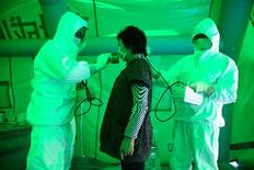Ειδικοί εξετάζουν μια κάτοικο της περιοχής κοντά στο πυρηνικό  εργοστάσιο της Φουκουσίμα για αυξημένα επίπεδα ραδιενέργειας.
